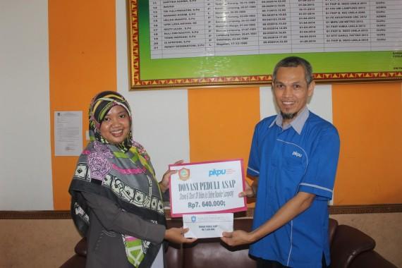 Kepala SD Islam Az Zahra Umi Fatirah menyerahkan dana untuk korban kabut asap di Riau kepada PKPU Lampung. | Ist