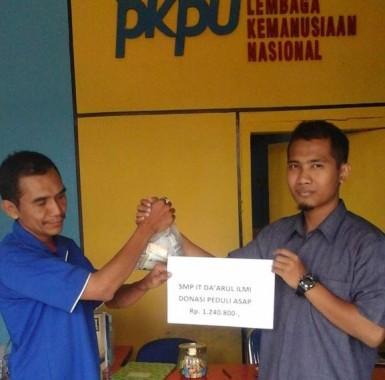 Perwakilan SMP IT Darul Ilmi (kanan) menyerahkan donasi untuk korban kabut asap kepada sraf PKPU Lampung (kiri), Selasa, 27/10/2015. | Ist