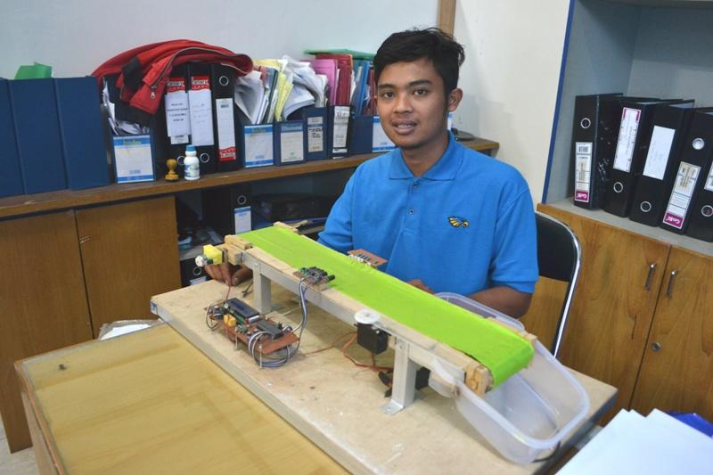 Aji Jamal, mahasiswa IBI Darmajaya membuat prototype alat pemisah dan penghitung barang cacat. | Ist.