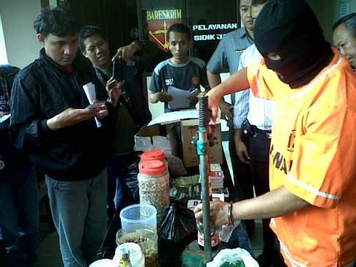 Tersangka pembuat jamu palsu sedang menunjukkan cara pengemasan jamu dalam ekspose di Polresta Bandar Lampung, Selasa, 17/11/2015 | Andi/jejamo.com