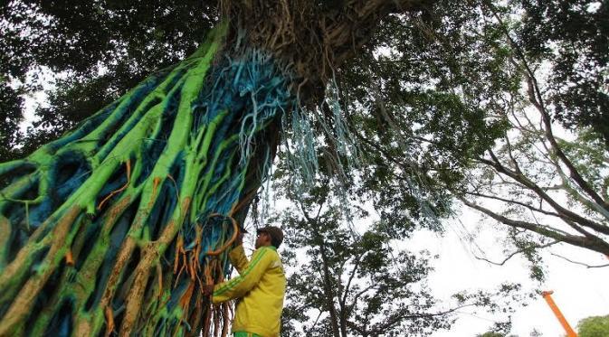 Pohon beringin yang berada di selatan Alun alun Merdeka Kota Malang, Jawa Timur dicat dengan komposisi warna hijau, biru dan oranye | Liputan6.com