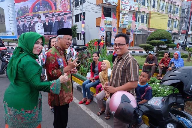 Calon Wali Kota Bandar Lampung Hi. Tobroni Harun menyapa dan membagikan bunga kepada para pelintas di kawasan Tugu Adipura, Minggu 8/11/2015.