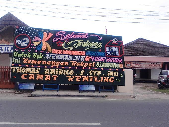 Salah satu papan ucapan ucapan selamat kemenangan Herman HN dan Yusuf Kohar terpampang di depan kantor Panwaslu Bandar Lampung. | Sugiono/Jejamo.com