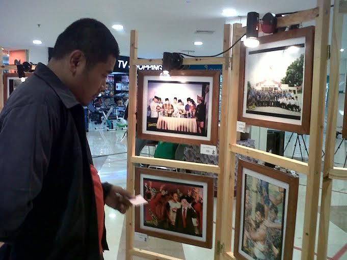 Salah satu pengunjung Mall Boemi Kedaton Bandar Lampung melihat hasil foto tentang pesta demokrasi di Bandar Lampung. | Widya/Jejamo.com