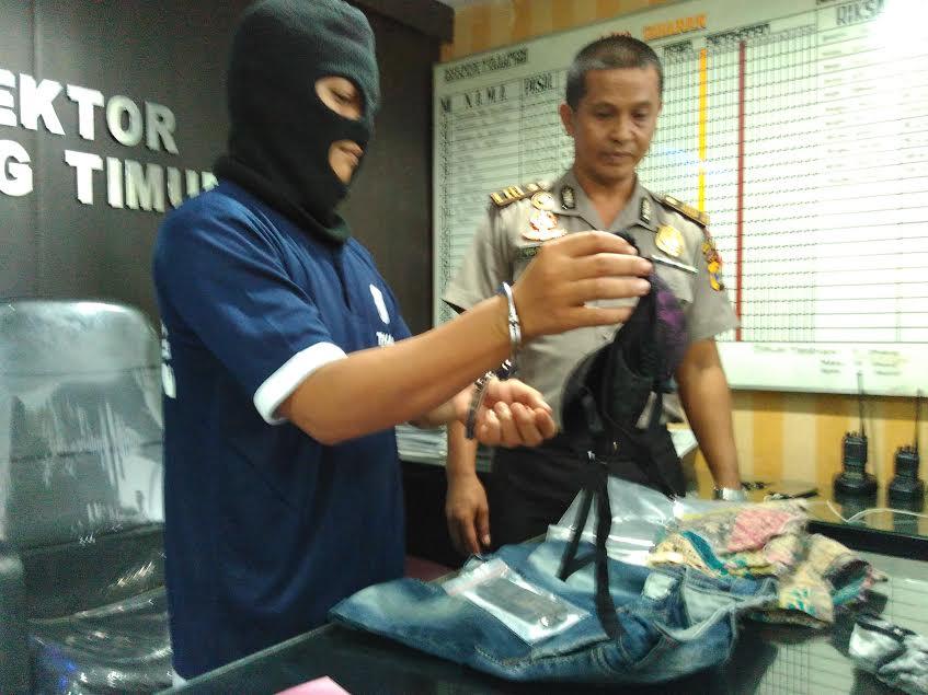 Tersangka pemerkosaan menunjukan salah satu barang bukti di Polsekta Tanjungkarang Timur, Selasa 1/12/2015. | Andi/Jejamo.com