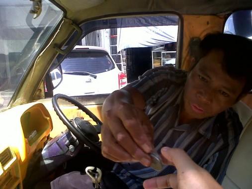 Andi sopir angkot jurusan Tanjungkarang-Way Halim sedang mengembalikan uang receh ongkos penumpang, Selasa, 12/1/2016. | Widyaningrum/jejamo.com