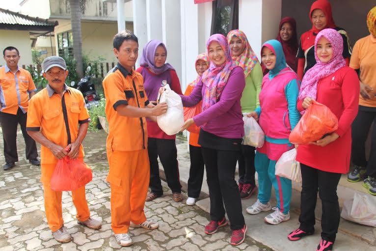 Ketua Dharma Wanita Kota Metro Elva Magdalena memberikan bantuan berupa sembako kepada para Petugas Kebersihan setempat, Jumat, 8/1/2016. | Tyas Pambudi/Jejamo.com
