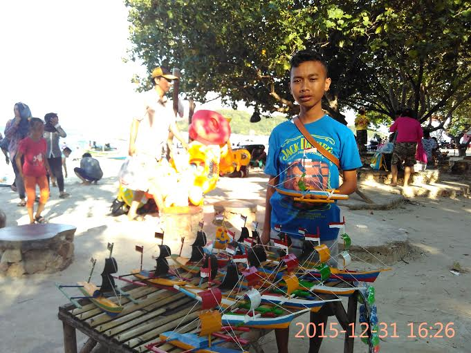 Tak seperti anak-anak lainnya, Rohman memanfaatkan liburan sekolahnya untuk berjualan cindera mata di Pantai Mutun. | Andi/Jejamo.com