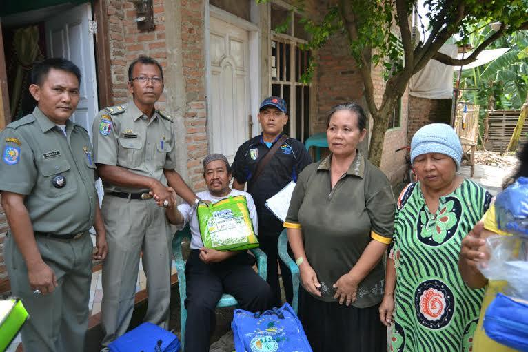 Sekretaris Dinsosnakertrans Pringsewu, Suhermanu menyerahkan bantuan kepada korban banjir di Pringsewu Barat, Kamis, 7/1/2016. | Nur Kholik/Jejamo.com
