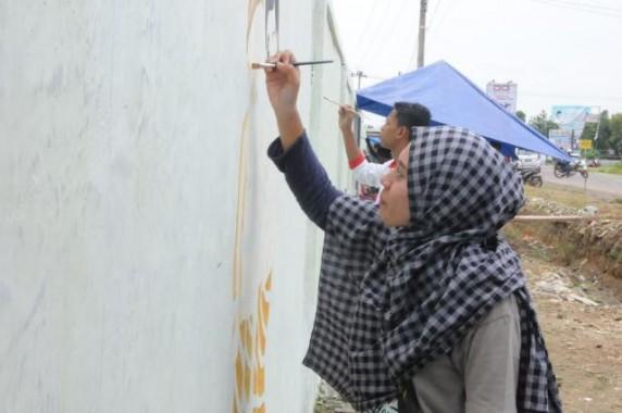Sejumlah warga membuat mural  di dinding pagar SMPN 4 Tulangbawang Tengah, Pulung Kencana, Selasa, 16/2/2016. | Ist