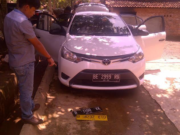 Petugas Polsek Abung Barat menunjukan plat kendaraan di mobil tersangka narkoba. | Lia/Jejamo.com
