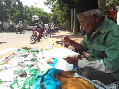 Abdul Somat sedang menikmati bekal makan siangnya di bawah terik matahari Kota Metro | Wahyu/jejamo.com