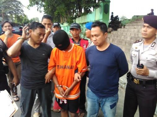 Tersangka pembunuh siswa SMKN 2 Bandar Lampung Dwiki Sopyan sedang menjalani olah TKP di Lapangan Saburai, Rabu, 9/3/2016. | Andi Apriyadi/Jejamo.com