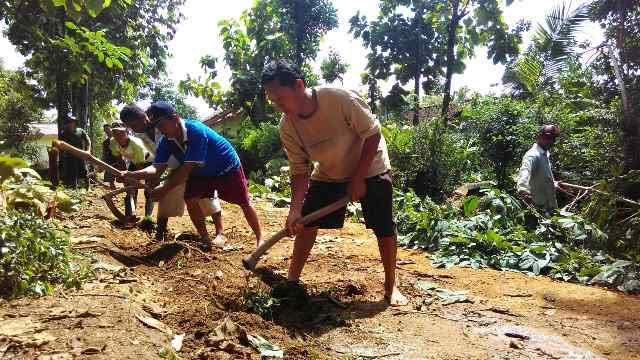 Karianto (paling depan) bersama masyarakat saat melakukan gotong royong, di jalan kampung Dusun 3 Kampung Kurniamataram, Kecamatan Seputihmataram, Kabupaten Lampung Tengah. | Raeza/Jejamo.com