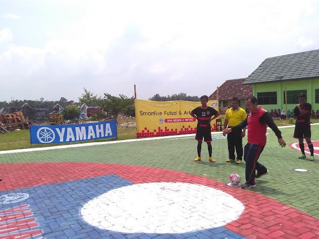 Kepala SMAN 5 Metro, Drs. Hanwar Priyo Handoko, saat melakukan tendangan pertama sebagai tanda pembukaan pelaksanaan lomba futsal dari rangkaian kegiatan Smanfive Futsal and Art Competition. | Wahyu/Jejamo.com
