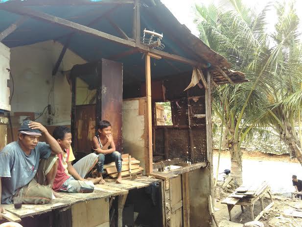 Iswanto bersama kedua anaknya sedang melihat Kondisi rumahnya yang hanyut. | Andi/Jejamo.com