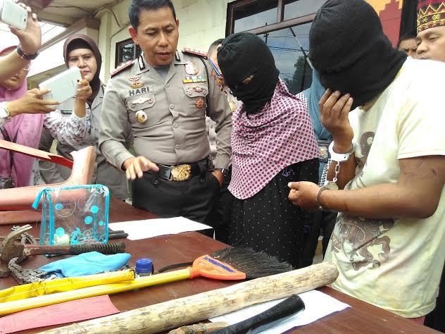 Pasangan suami istri, Ek dan Su digelandang Polresta Bandar Lampung usai ditetapkan tersangka kasus penganiayaan terhadap anaknya. | Andi/Jejamo.com