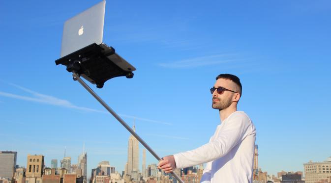 Seorang pria menggunakan laptop untuk selfie. | Ist.