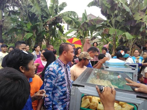 Sejumlah warga berebut kue yang dibeli Wali Kota Bandar Lampung Herman HN di sekitar lokasi kebakaran pabrik keripik singkong di Sukarame, Kamis, 7/4/2016. | Andi Apriyadi/Jejamo.com