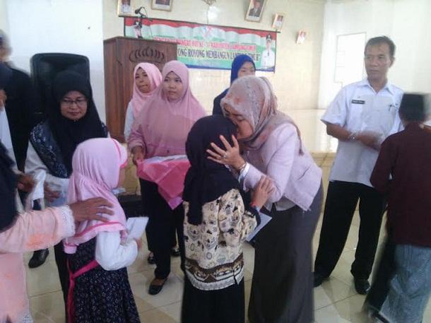 Bupati Lampung Timur Chusnunia Chalim mencium salah satu anak yatim piatu dalam acara penyerahan bantuan bagi kaum duafa dan anak yatim, Rabu, 27//2016. | Parman/Jejamo.com