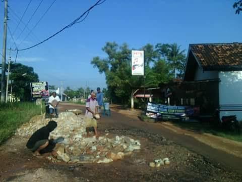 Warga Desa Tanjungkencono, Kecamatan Way Bungur, Lampung Timur memperbaiki jalan yang rusak secara gotong royong, Kamis, 12/5/2016. | Suparman/Jejamo.com