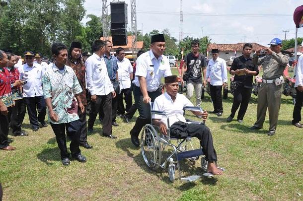 Bupati Lampung Tengah, Mustafa mendorong kursi roda penyandang cacat yang memperoleh bantuan kursi roda. | Raeza/Jejamo.com