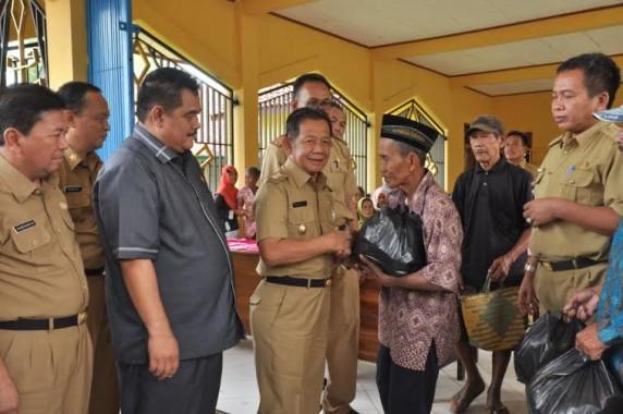 Wakil Bupati Tulang Bawang Barat Fauzi Hasan menyerahkan sembako kepada lansia pada acara pasar murah di Tiyuh Kartaraharja, Senin, 20/6/2016 | Mukadam/jejamo.com
