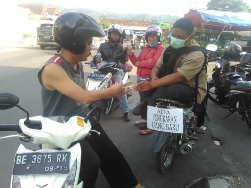 Andre (baju coklat) menjajakan jasa penukaran uang di dekat Terminal Kemiling Bandar Lampung, Senin, 4/7/2016. | Andi Apriyadi/Jejamo.com