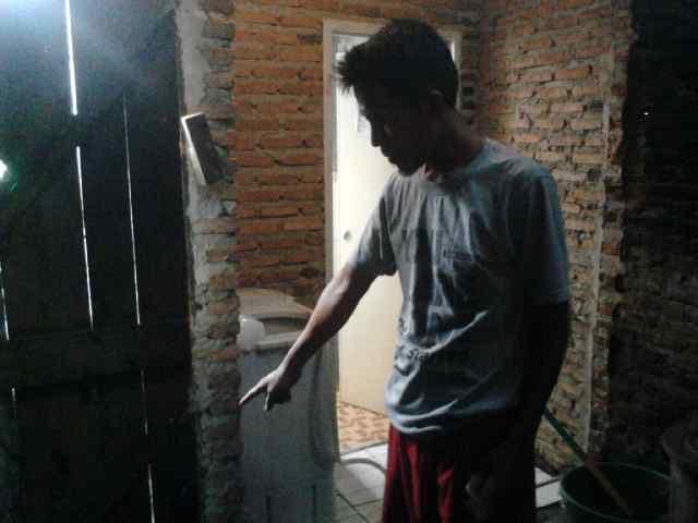 Tabah menunjukkan bagian pintu belakang rumahnya yang rusak dibobol maling |  Sugiono/jejamo.com