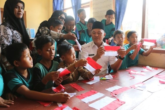 Bupati Lampung Tengah, saat membuat bendera bersama murid-murid Sekolah dasar di Kabupaten setempat | Raeza/jejamo.com
