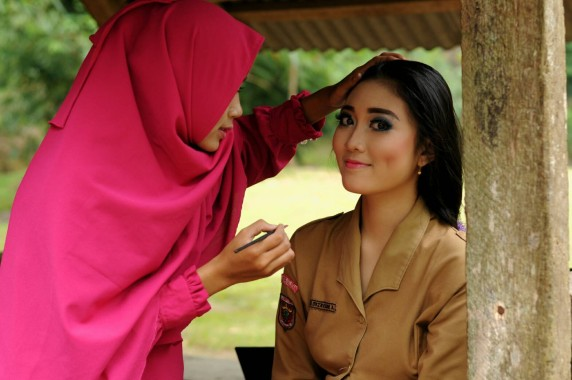 Novi (kiri) sedang menata rias wajah model Lampung Luki Oktaviani Brillian (Uki). | Ist