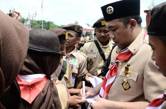 Bupati Tulang Bawang Barat Umar Ahmad, SP melayani permintaan anggota pramuka degan memberi tanda tangan di dasi pramuka dalam acara  HUT Pramuka Ke-55 dengan menaiki kereta Rato yang berlangsung di Lapangan Tiyuh Candra Kencana | ist