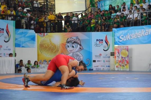 Maya Octa Sari, memakai wrestling suit berwarna merah, mengunci setelah berhasil membanting Novi Ardila, asal Sumatera Barat, di pertandingan Gulat kelas 75kg PON XIX Jabar 2016, Senin 26/9/2016, GOR Saparua, Kota Bandung | Arif/jejamo.com