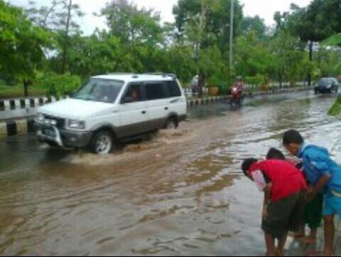 Jalan Jenderal Sudirman, persisnya di depan halte SMAN 2 Metro, digenangi air saat hujan deras turun, Sabtu, 15/10/2016. | Aris Sahputra/Jejamo.com