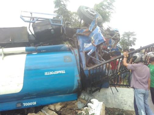 Warga sedang mengevakuasi jenazah sopir truk tangki solar yang terguling di Jalan Pramuka, Rajabasa, Bandar Lampung, Rabu, 12/10/2016 | Andi/jejamo.com