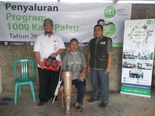 Kepala Cabang IZI Lampung Agus Rin Wirawan (kanan) menyalurkan kaki palsu kepada salah seorang penerima, didampingi staf IZI Lampung Tomy. | Istimewa